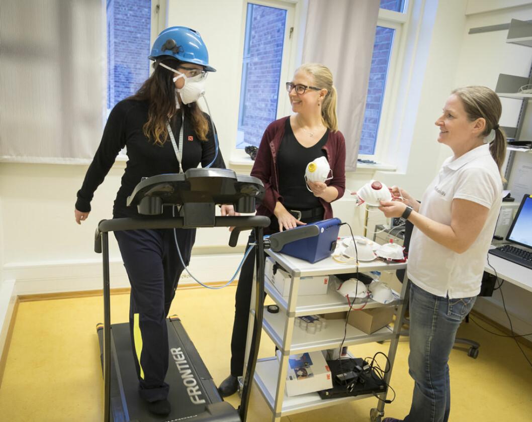 """Her prøvekjøres testopplegg som er brukt til utprøving av støvmasker i """"smelteverks-Norge"""". Yrkeshygieniker Solveig Føreland (til høyre) er ansvarlig for målingene, mens SINTEF-forsker Ida Teresia Kero er prosjektleder for det tverrfaglige prosjektet målingene inngår i. Testperson på tredemølla er SINTEFs Ida Eir Lauritzen. (Foto: Thor Nielsen/SINTEF)"""