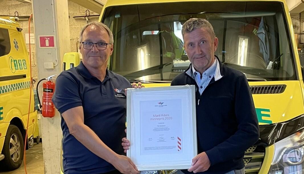 FoU-direktør Tom Hanssen i Stiftelsen Norsk Luftambulanse deler ut prisen til klinikksjef Pål Madsen ved Helgelandssykehuset.